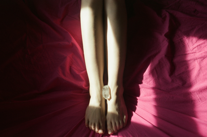 """""""a photoof a piece of crystal is placed between a woman's feet who is in bed on red bedsheets from Lina Scheynius photo-essay for Tabayer jewelry Tabayer jewellery"""""""